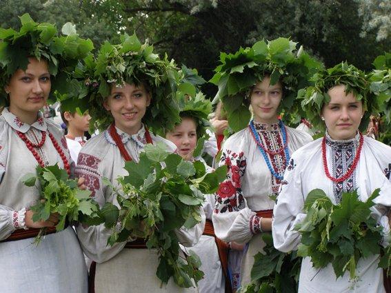 Красиві дівчата у вишиванках плетуть вінки на зелені свята